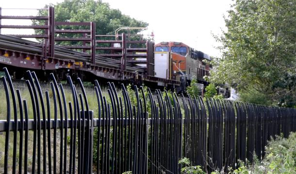 a two engine train waiting for the all clear to move into the yard for load-up and adding on of extra cars.