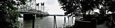 in this snap the distance from right to left could not be expressed in one shot other than using a panoramic setting which compressed image; on the right the walk way up to the red lion inn and restaurant, on the left the interstate bridge between oregon and washington state.