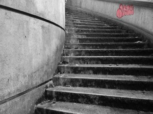 The lines on the wall and stairs curve, have mold growing with graffitti